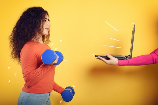 Ragazza con manubri pronta per iniziare la palestra online con un computer.