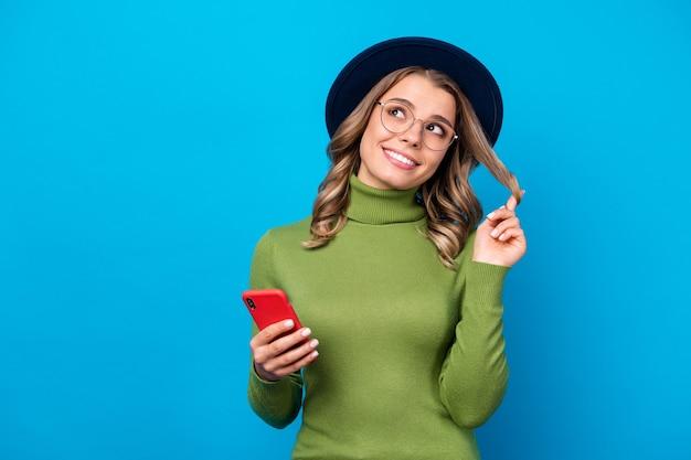 Ragazza con cappello e occhiali tenendo il telefono