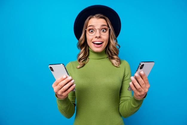 Ragazza con cappello e occhiali che tengono i telefoni