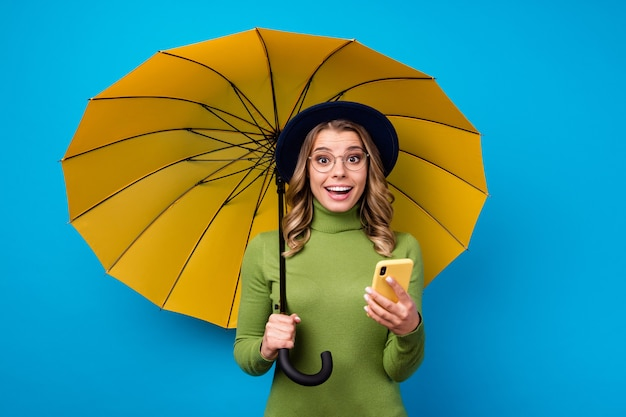 Ragazza con cappello e occhiali tenendo ombrello e telefono