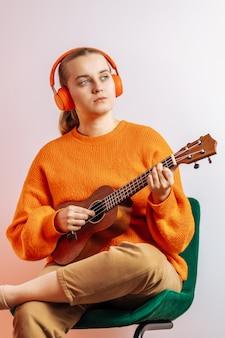 Una ragazza con le cuffie suona l'ukulele