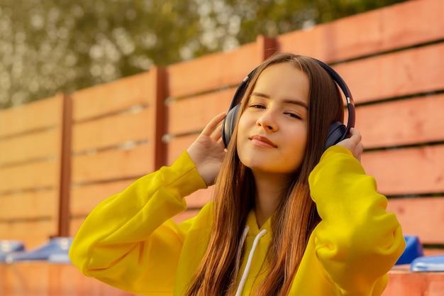 Una ragazza con le cuffie in una giornata di sole ascoltando musica sul suo telefono cellulare, stile di vita estivo