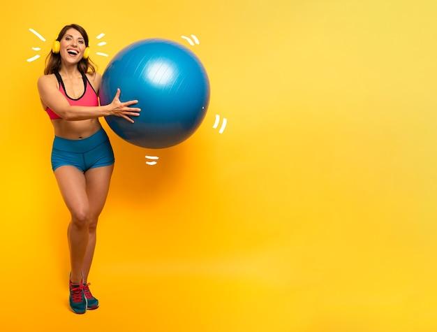 La ragazza con la cuffia avricolare tiene una superficie gialla della sfera di ginnastica