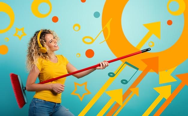 La ragazza con le cuffie usa la scopa come una chitarra
