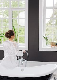Ragazza con la schiena in una veste di seta bianca in un lussuoso bagno