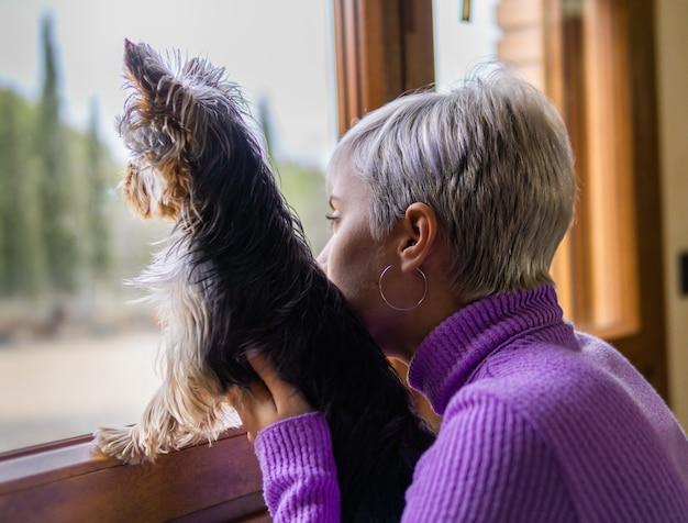 Ragazza con il suo cane che guarda fuori dal confinamento della finestra