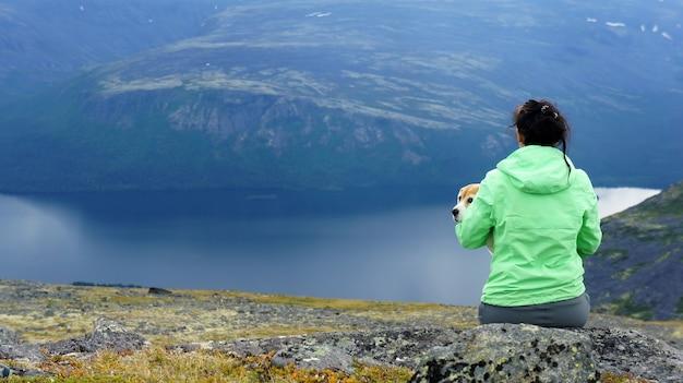 Ragazza con il suo cane che riposa all'aperto in montagna
