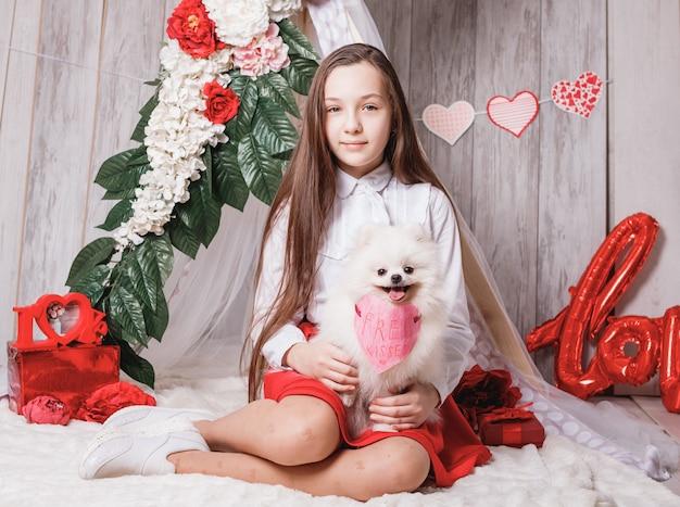 Ragazza con il suo felice carino soffice cane bianco pomerania con baci gratis cuore di carta, concetto di san valentino