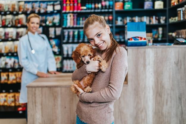 Ragazza con il suo cucciolo di barboncino dal veterinario.