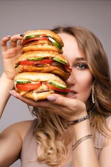 Ragazza con enorme hamburger a portata di mano. ritratto in studio di giovane donna bruna in t-shirt bianca che tiene enormi hamburger sulla sua mano che sembra scioccata o sorpresa a porte chiuse.