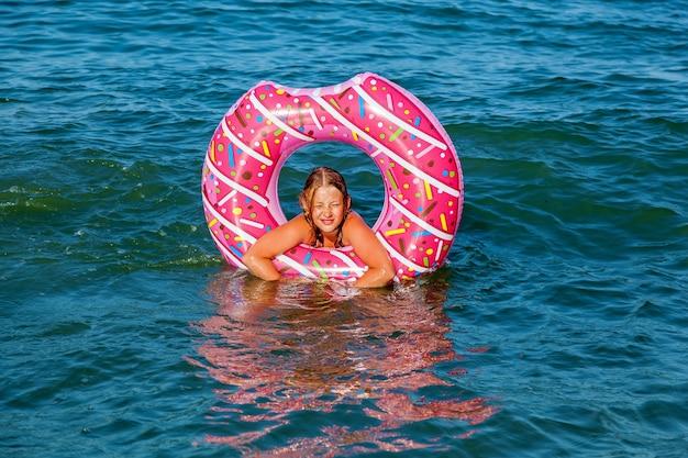 Una ragazza con un cerchio gonfiabile a forma di ciambella sta facendo il bagno in mare. vacanza in famiglia al mare