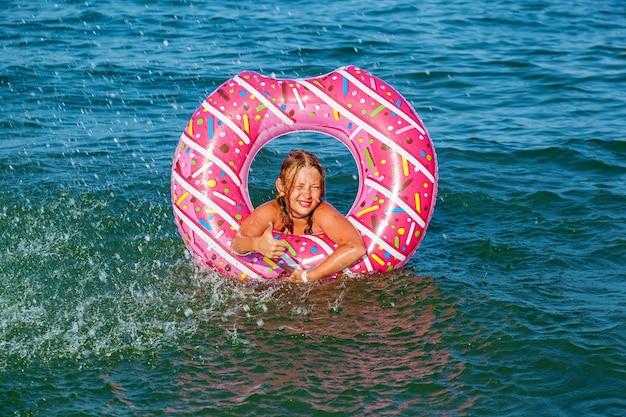 Una ragazza con un cerchio gonfiabile a forma di ciambella sta facendo il bagno in mare