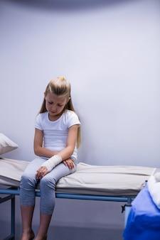 Ragazza con la mano ferita che si siede sul letto della barella