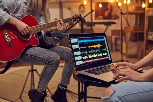 Ragazza con il computer portatile che registra musica suonata da una giovane donna con la chitarra