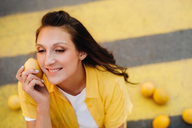 Una ragazza con i limoni in una camicia gialla, pantaloncini e scarpe nere siede su un passaggio pedonale giallo in città. l'umore del limone.