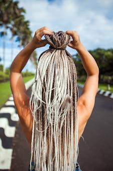 Una ragazza con lunghe trecce africane, vista posteriore