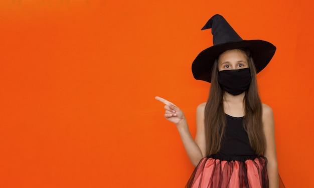 La ragazza con lunghi capelli castani con cappello e costume da strega su halloween indica un messaggio pubblicitario