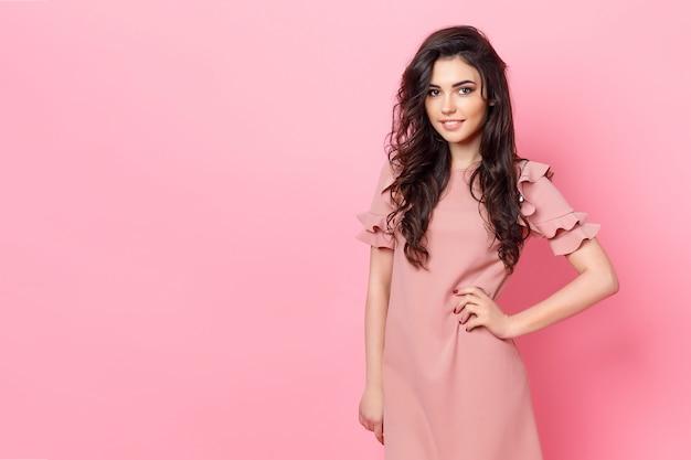 Ragazza con lunghi capelli ricci in un abito rosa.