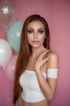 Ragazza con lunghi capelli ricci in posa su uno sfondo rosa. ritratto di una giovane donna sorridente felice.