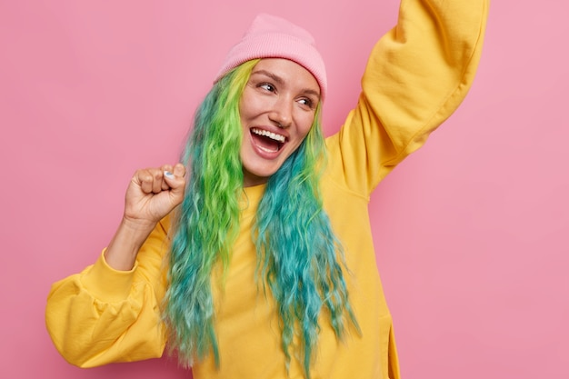 La ragazza con i capelli lunghi tinti fa ballare il campione alza le mani guarda felicemente lontano sembra che il vincitore indossi un cappello e un maglione giallo isolato sul rosa