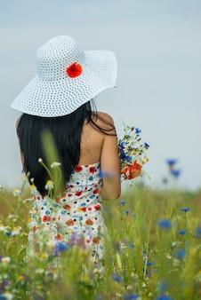Ragazza con i capelli lunghi in un vestito e un cappello bianco con fiori di papavero sta con in un prato in fiore con un mazzo di fiori di campo.