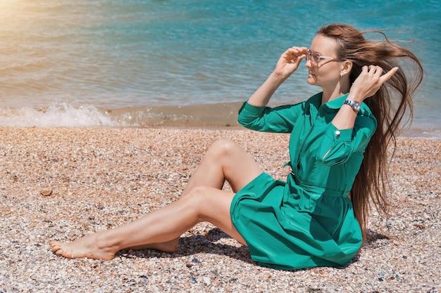 Una ragazza con i capelli lunghi in un vestito verde sulla spiaggia. vacanze al mare