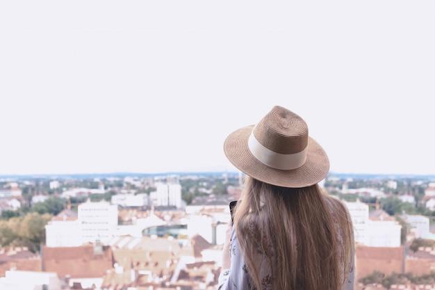 Una ragazza con i capelli lunghi in un cappello si trova sul ponte di osservazione e guarda la città di graz.
