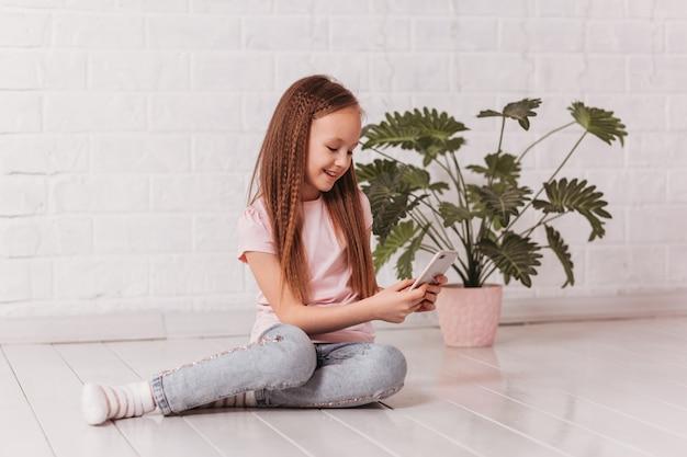 Una ragazza con i capelli lunghi si siede sul pavimento e guarda in uno smartphone