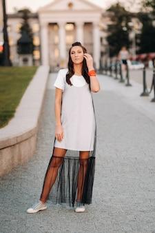 Una ragazza con i capelli lunghi con orecchini rossi in abiti bianchi cammina per la città. la modella tiene i capelli tra le mani e sorride.