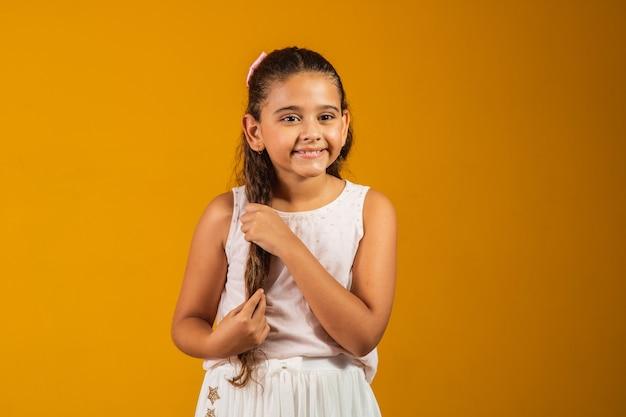 Ragazza con lunghi capelli ondulati sani. bellezza, aspetto, acconciatura. modello bambino con sorriso sul viso carino su sfondo giallo. bambino felice, concetto di infanzia. gioventù, cura e salute.