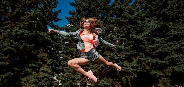 Una ragazza con le gambe lunghe in pantaloncini e una camicetta arancione salta come una ballerina. panorama banner