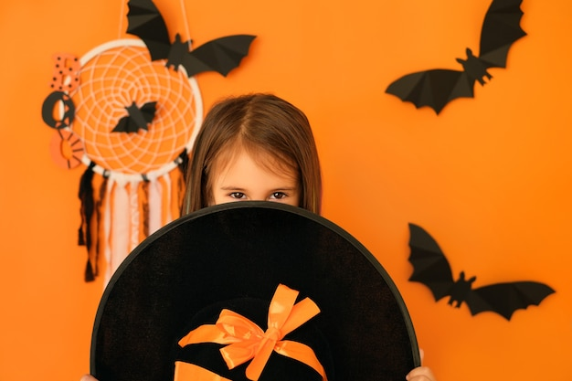 Una ragazza con uno sguardo malizioso guarda da dietro un grande cappello da strega in attesa di halloween