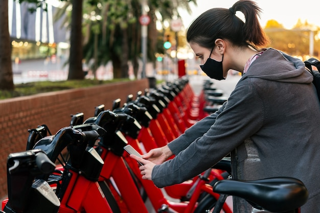 Ragazza con la maschera che esegue la scansione del codice per sbloccare una bicicletta