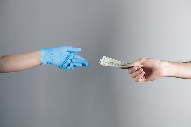 Ragazza con guanto medico tenendo i soldi