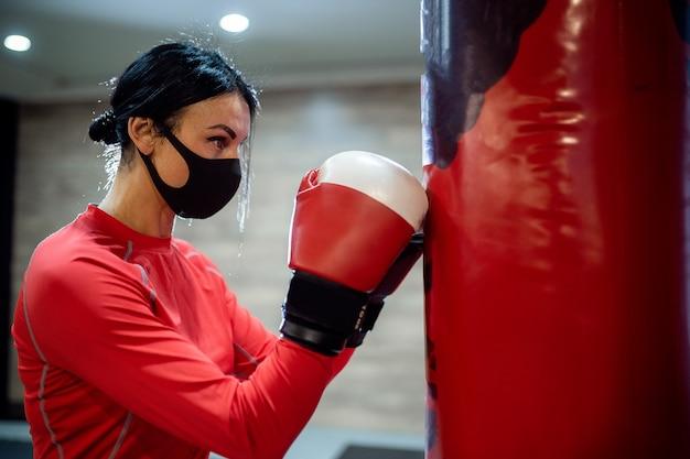 Ragazza con una mascherina medica e guantoni da boxe.