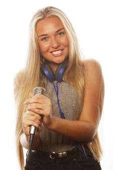 Ragazza con un microfono che canta e si diverte, isolata su bianco Foto Premium