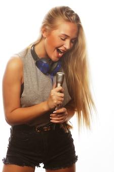 Ragazza con un microfono che canta e si diverte, isolata su bianco