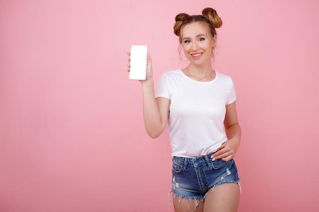 Ragazza con telefono finto su spazio rosa