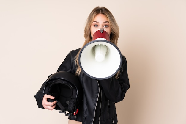 Ragazza con un casco da motociclista sul muro beige che grida attraverso un megafono