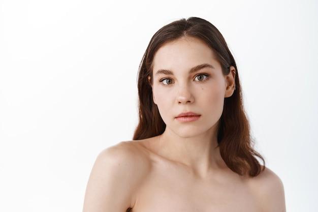 Ragazza con le spalle nude, pelle del viso pulita e idratata, in piedi su un muro bianco