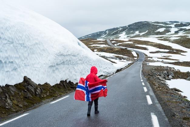 Ragazza con una bandiera norvegese su una strada di montagna in norvegia