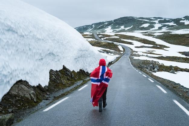 Ragazza con una bandiera norvegese su una strada innevata in norvegia