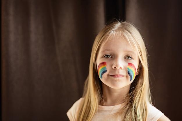 Ragazza con arcobaleno dipinto sul viso durante la quarantena covid-19