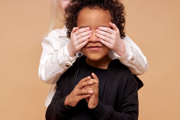 Ragazza con la pelle pallida che chiude gli occhi del ragazzo afro dal retro