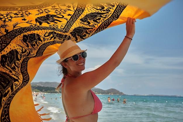 Ragazza con un pareo in riva al mare durante le vacanze estive