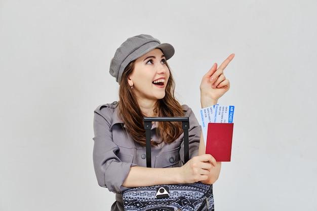 Una ragazza con un passaporto, biglietti aerei con bagagli attende un invito a terra.