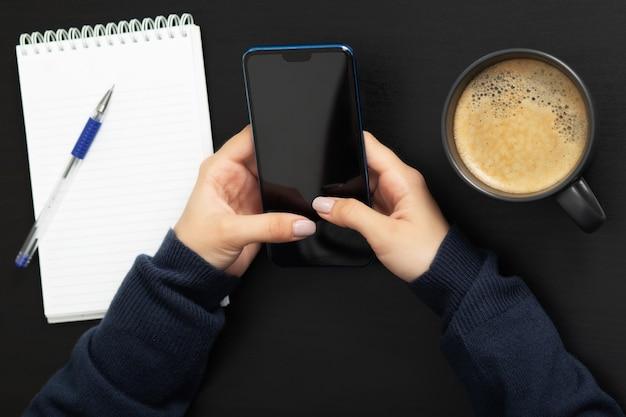 Ragazza con un telefono al tavolo con un business mockup di caffè e blocco note