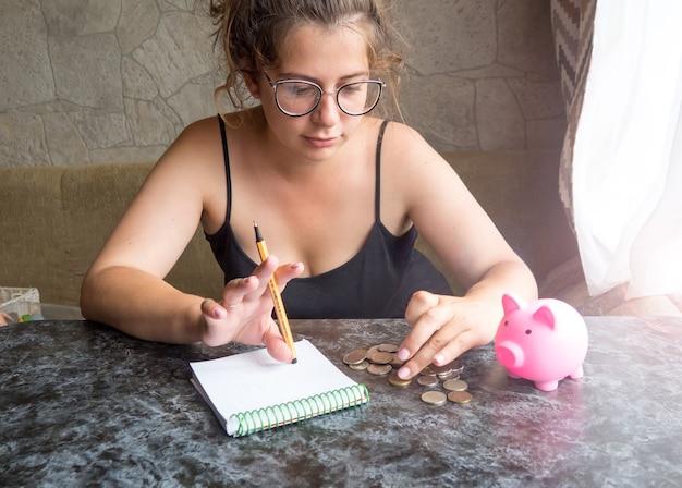 Una ragazza con un salvadanaio, non ha soldi, guarda i soldini e piange. conta spese e utenze, povertà