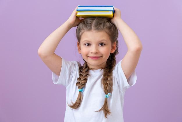 Una ragazza con le trecce in una maglietta bianca e libri in mano su uno sfondo isolato.