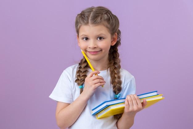 Una ragazza con le trecce in una maglietta bianca e libri in mano su uno sfondo viola isolato.